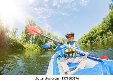 Happy kids kayaking on the river. Active girl with her brother having fun and enjoying adventurous experience with kayak on a sunny day during summer vacation