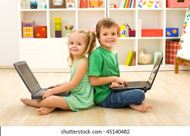 Happy kids with laptops sitting on the floor in their room