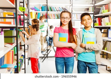 Happy kids in library stand together with  books