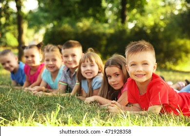 Happy kids lying on grass in park