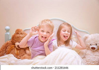 Happy kids make faces, cute brother and sister make grimace, having fun at home, lovely family, active childhood concept