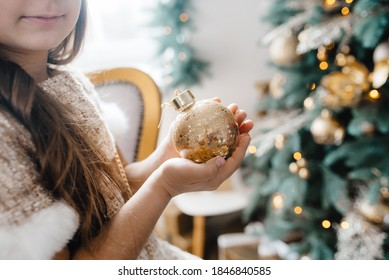 happy kids model girl with long hair sitting at home near window and Christmas tree holding golden sparkling ball in hands