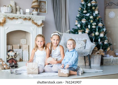 Happy kids near Xmas tree with presents near fireplace