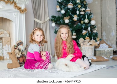 Happy kids near Xmas tree with white dog with presents near fireplace