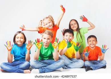 Happy kids with painted hands smiling and posing at white background.