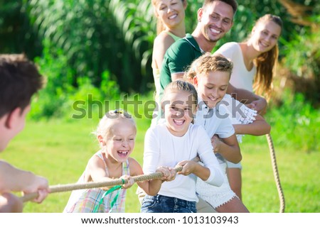 Happy Kids With Parents Playing Active Games In Summer Park Tugging War