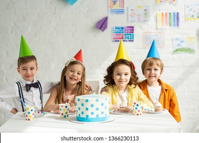 happy kids in party hats sitting at table with cake and looking at camera while celebrating birthday together
