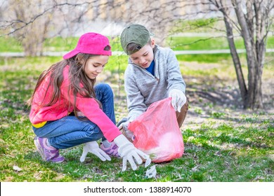Happy kids picking up trash in the spring park