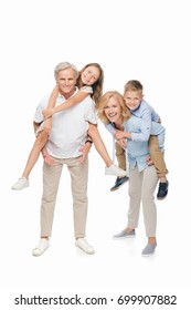 happy kids piggybacking on grandparents isolated on white