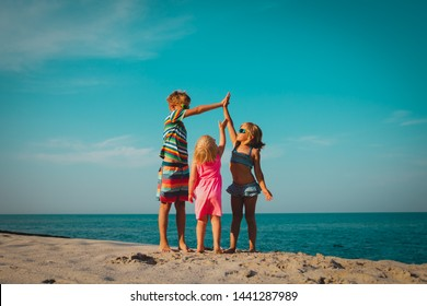happy kids play on beach, boy and girls have fun at sea