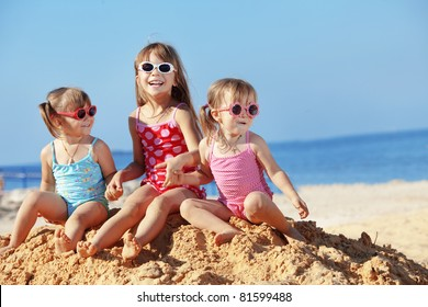 Happy kids playing at the beach in summer