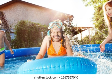 Happy kids playing in blue water of swimming pool