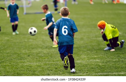 Happy Kids Playing Football Game. Sports League for Kids. Group of School Boys Kicking Soccer Tournament Match. School Boys in Soccer Jersey Kits Compete on Grass Field