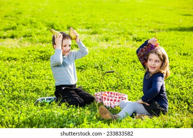 happy kids playing with fruits from picnic basket sitting on the green grass