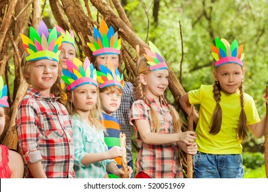 Happy kids playing Injuns standing next to wigwam