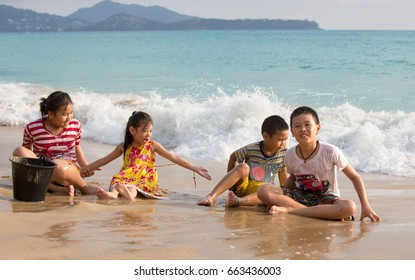 Happy kids playing on beach sand on summer.