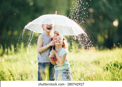 happy kids playing outdoor in raining spring park. shallow depth of field,focus on children or raindrops