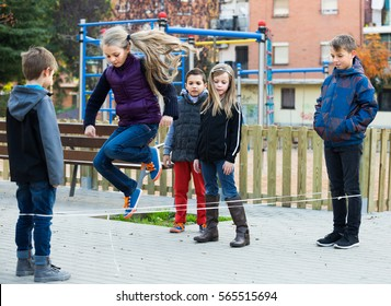Happy kids  playing rubber band jumping game and laughing outdoors