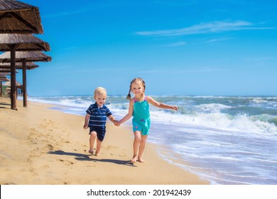 happy kids playing in a summer sea, running together along the beach ocean, fun game for boy and girl