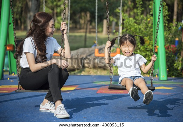 happy kids playing a swing with her mother in a park
