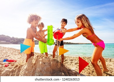 Happy kids playing with water and sand on beach