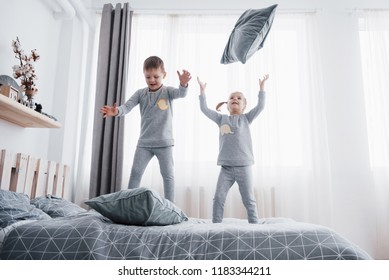 Happy kids playing in white bedroom. Little boy and girl, brother and sister play on the bed wearing pajamas. Nightwear and bedding for baby and toddler. Family at home.