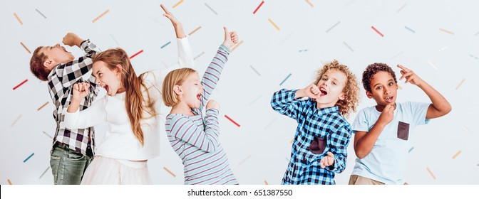 Happy kids pretending to sing at the school party