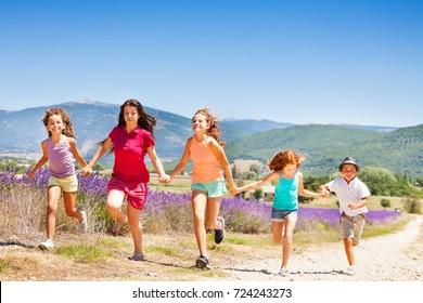 Happy kids running together through lavender field