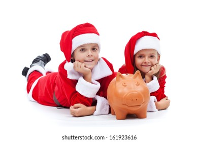 Happy kids saving for the christmas presents - laying with their piggy bank, isolated