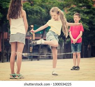 Happy kids in school age playing together with chinese jumping rope outdoors