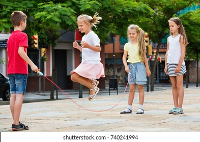 Happy kids in school age playing together with jumping rope outdoors