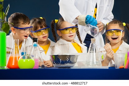 Happy kids with scientist doing science experiments in the laboratory