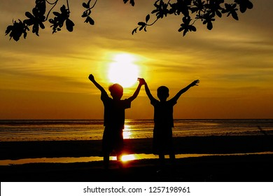 Happy kids silhouette with open arms during golden sunset in the tropical beach.