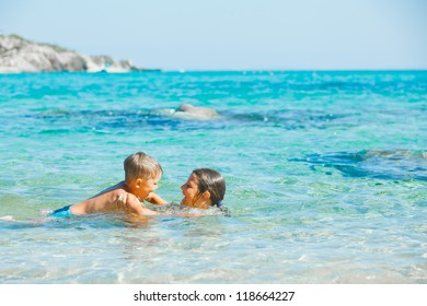Happy kids. Sister and brother playing and swimming in the transparent sea