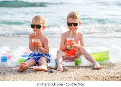 Happy kids sitting on an air mattress and drink juices. Summer vacation concept.