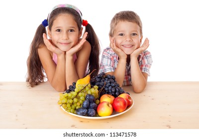 Happy kids sitting on the table with plate of fruit, isolated on white