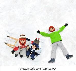 Happy kids with sledding on snow ground