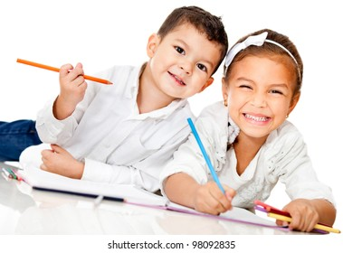 Happy kids smiling and coloring a book - isolated over white