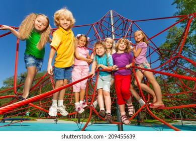 Happy kids stand on red ropes of playground