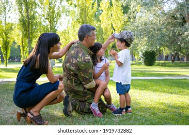 Happy kids and their mom meeting military dad in uniform outdoors. Boy trying on camouflage cap. Family reunion or returning home concept
