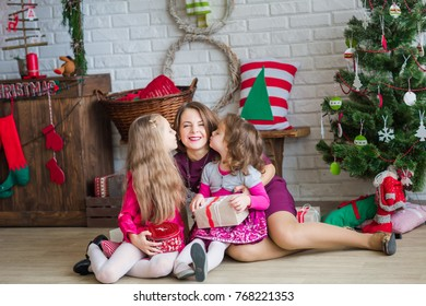 Happy kids with their mother near Xmas tree with presents near fireplace