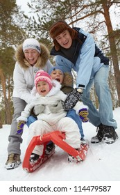 Happy kids and their parents riding on sledge in park