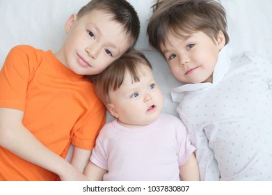 happy kids, three laughing children different ages lying, portrait of boy, little girl and baby girl, happiness in childhood of siblings, living in big family with three children