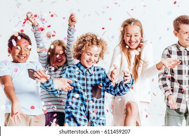 Happy kids throwing colorful confetti in a room