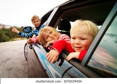 happy kids travel by car on road in nature
