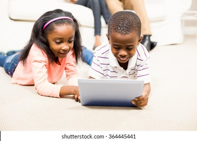 Happy kids using tablet pc beside their parents