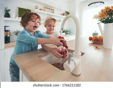 happy kids washing cherries under tap water in the kitchen