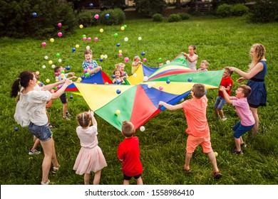 Happy kids waving rainbow parachute full of balls