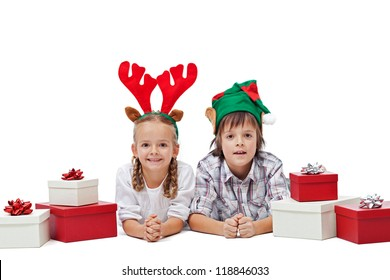 Happy kids wearing elf and reindeer hats laying with presents - the magic of christmas, isolated