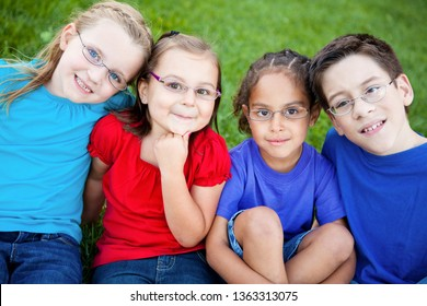 Happy Kids Wearing Glasses Sitting Together in Grass Outside - Portrait